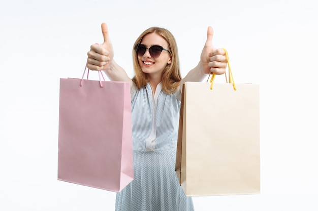 Jovem mulher posando com sacolas de presente, regozijando-se e mostrando compras