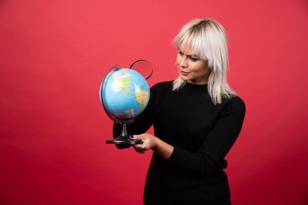 Jovem mulher posando com um globo sobre um fundo vermelho. foto de alta qualidade