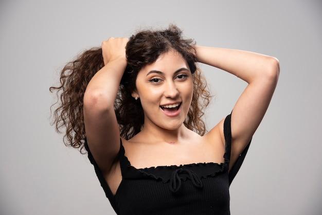 Jovem mulher posando de blusa preta com cabelo encaracolado. foto de alta qualidade