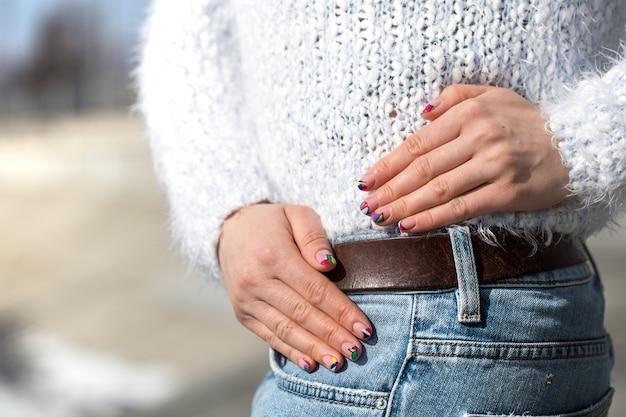 Jovem mulher posando de jeans ao ar livre