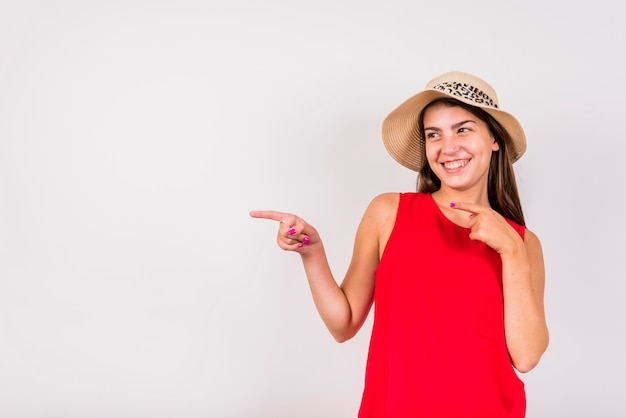 Jovem mulher posando e apontando para fora no fundo branco