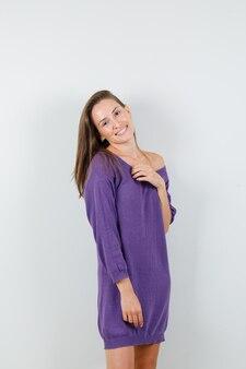 Jovem mulher posando em pé com a camisa violeta e atraente. vista frontal.