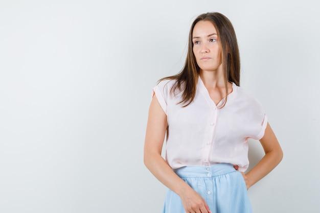 Jovem mulher posando em pé com camiseta, saia e parecendo confiante. vista frontal.