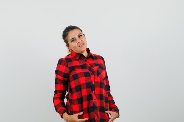 Jovem mulher posando em pé com uma camisa e olhando confiante, vista frontal.