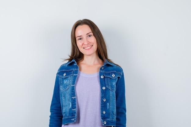 Jovem mulher posando em t-shirt, jaqueta jeans e olhando feliz. vista frontal.