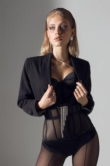 Jovem mulher posando em um estúdio fotográfico, elegante mulher em meia-calça copron e espartilho. foto de alta qualidade