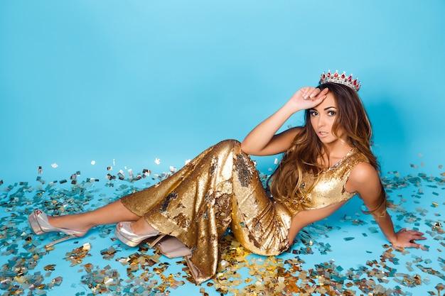 Jovem mulher posando em vestido dourado com coroa