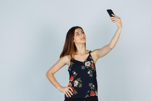 Jovem mulher posando enquanto toma selfie em smartphone na blusa e parece confiante, vista frontal.