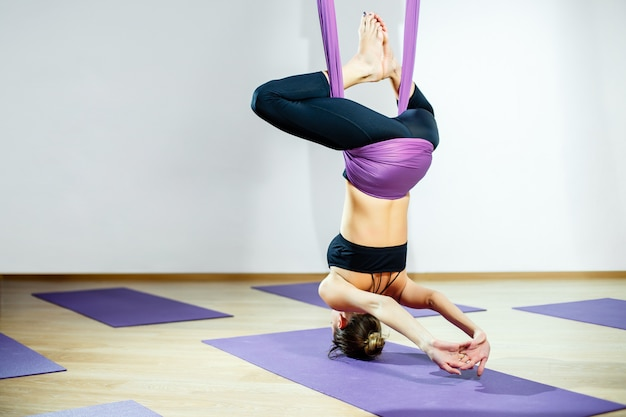 Jovem mulher posando fazendo exercícios de ioga aérea com rede