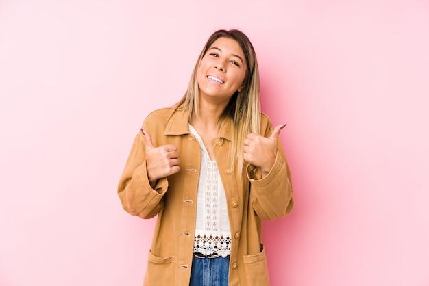 Jovem mulher posando levantando os dois polegares, sorrindo e confiante