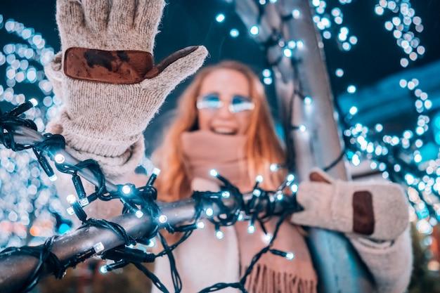 Jovem mulher posando na rua com árvores iluminadas