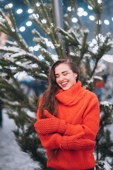 Jovem mulher posando perto da árvore de natal na rua