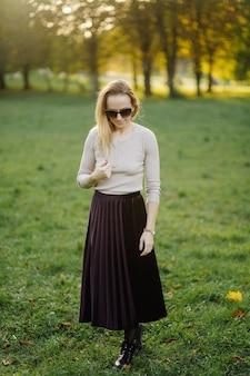 Jovem mulher posando sobre folhas amarelas no parque do outono. ao ar livre