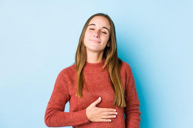 Jovem mulher posando toca a barriga, sorri suavemente, comendo e conceito de satisfação.