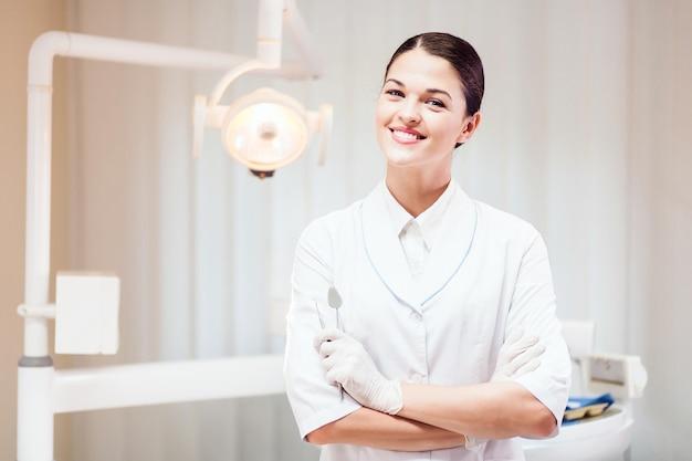 Jovem mulher posar médico no consultório do dentista