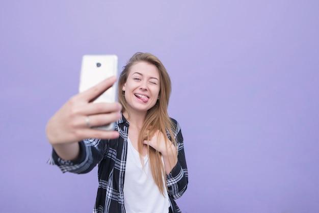 Jovem mulher positiva que levanta e que faz um selfie em um fundo roxo isolado. garota feliz pega-se em um smartphone.