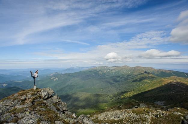 Jovem mulher pratica ioga no topo de uma montanha