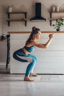 Jovem mulher praticando agachamento. mulher fazendo exercícios em casa.