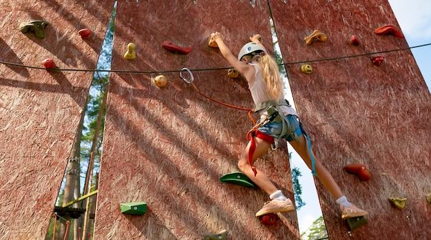 Jovem mulher praticando escalada em uma parede de pedra dentro de casa