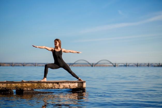 Jovem mulher praticando exercícios de ioga no cais de madeira tranquila com a cidade esporte e recreação na cidade apressar