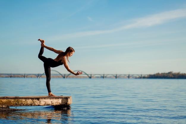 Jovem mulher praticando exercícios de ioga no cais de madeira tranquila com cidade. esporte e recreação na cidade
