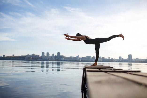 Jovem mulher praticando exercícios de ioga no cais de madeira tranquila com cidade