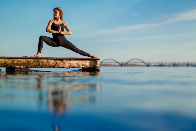Jovem mulher praticando exercícios de ioga no cais de madeira tranquila