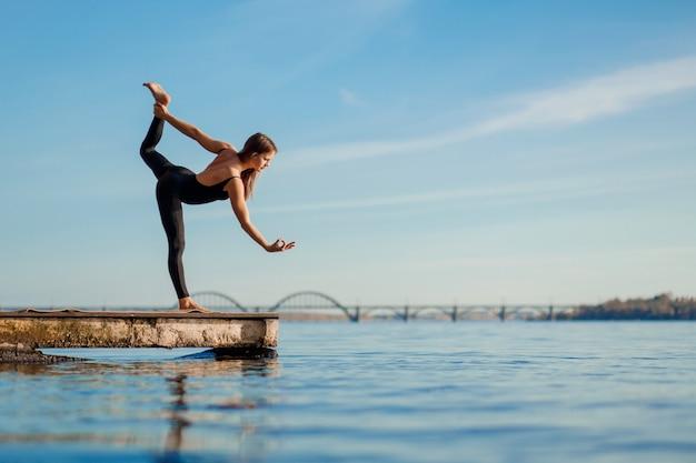Jovem mulher praticando exercícios de ioga no cais de madeira tranquilo com fundo de cidade. esporte e recreação na cidade