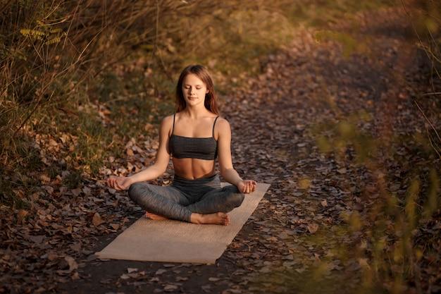 Jovem mulher praticando exercícios de ioga no parque outono com folhas amarelas. estilo de vida esportivo e recreativo