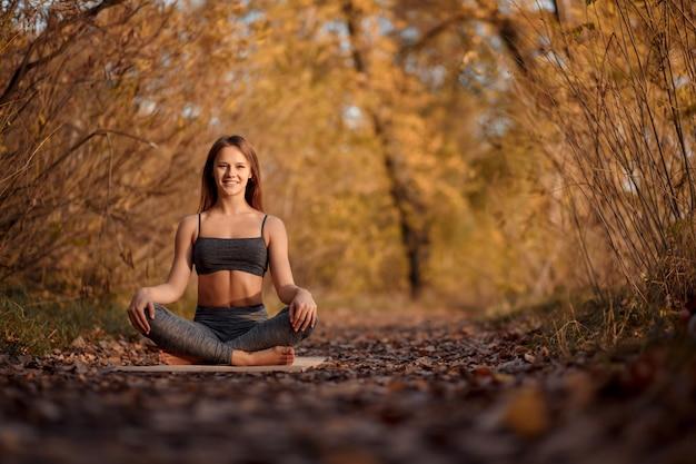 Jovem mulher praticando exercícios de ioga no parque outono com folhas amarelas.