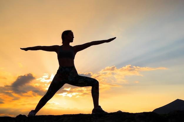 Jovem mulher praticando ioga ao pôr do sol na localização da bela montanha.