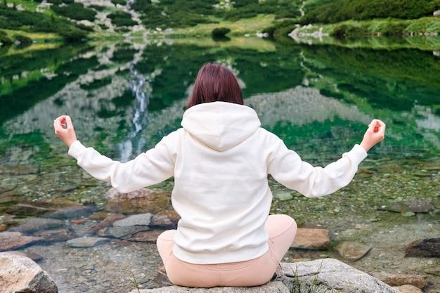 Jovem mulher praticando ioga e meditando na margem do lago com água transparente e cachoeira refletida nela. férias e feriados nas montanhas. relaxamento na natureza.