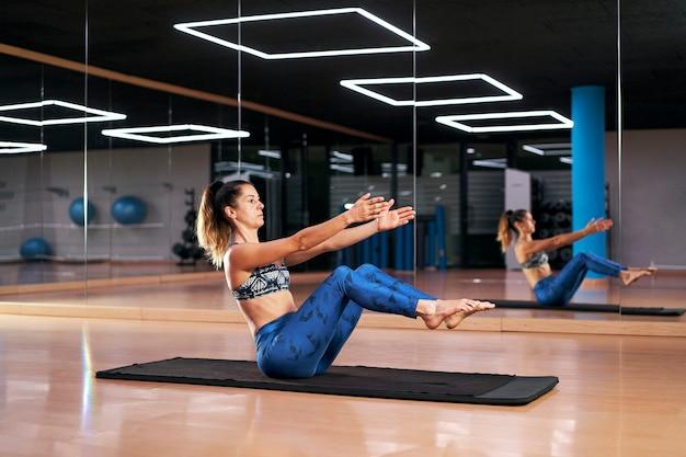 Jovem mulher praticando ioga em um ginásio, exercitando-se em roupas esportivas azuis, fazendo pose de barco ou agnistambhasana.