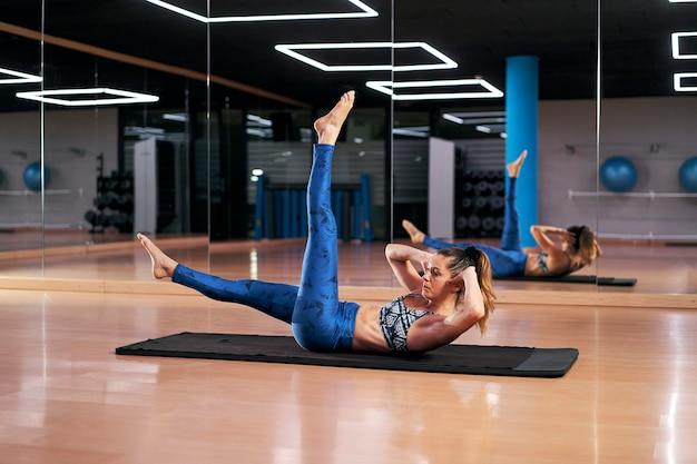 Jovem mulher praticando ioga em um ginásio fazendo pose cruzada. silhueta de corpo inteiro.