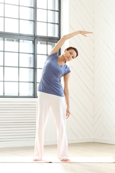 Jovem mulher praticando ioga em um tapete de ioga