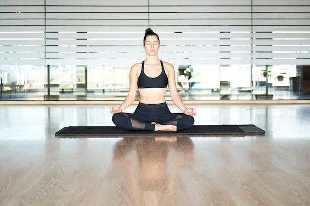 Jovem mulher praticando ioga em uma academia, fazendo exercícios em uma roupa esportiva preta, fazendo exercícios de meditação.