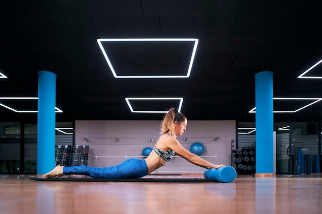 Jovem mulher praticando ioga em uma academia, malhando em uma roupa esportiva preta, fazendo alguns exercícios de rolo de pilates.