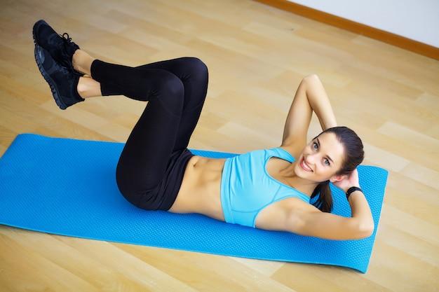 Jovem mulher praticando ioga, fazendo coisa selvagem, exercício flip-the-dog, pose de camatkarasana, malhando, vestindo roupas esportivas, calça preta e blusa, comprimento total interior, parede cinza no estúdio de yoga