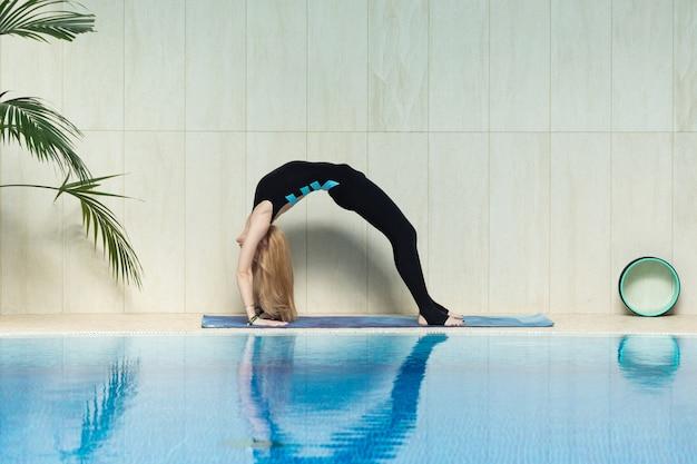 Jovem mulher praticando ioga interior na zona térmica da piscina.