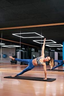 Jovem mulher praticando ioga ou pilates em uma academia, fazendo exercícios com roupas esportivas azuis, fazendo vasisthasana ou prancha lateral. silhueta de corpo inteiro.
