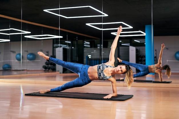 Jovem mulher praticando ioga ou pilates em uma academia, fazendo exercícios com roupas esportivas azuis, fazendo vasisthasana ou prancha lateral.