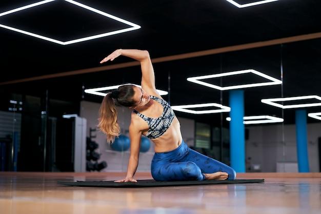 Jovem mulher praticando ioga ou pilates em uma academia, se exercitando em uma roupa esportiva azul, fazendo exercícios de alongamento.
