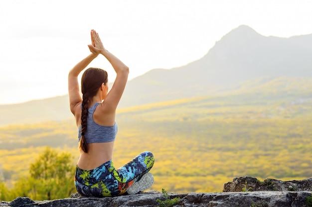 Jovem mulher praticando ioga ou pilates no pôr do sol ou nascer do sol na localização bonita montanha.