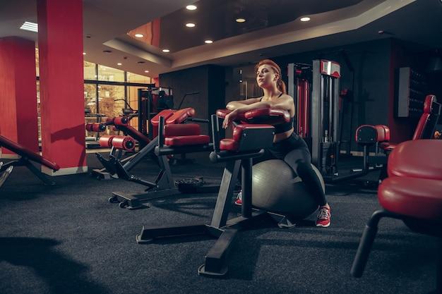 Jovem mulher praticando na academia com o equipamento. modelo feminino atlético fazendo exercícios, treinando corpo