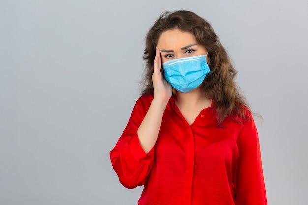 Jovem mulher preocupada com blusa vermelha e máscara protetora médica, parecendo doente com a mão perto da cabeça e com dor de cabeça sobre um fundo branco isolado