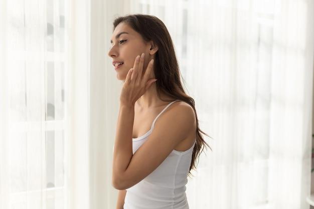 Jovem mulher preocupada com rugas no rosto. garota aplicando loção, desfrutando de cuidados com a pele saudáveis