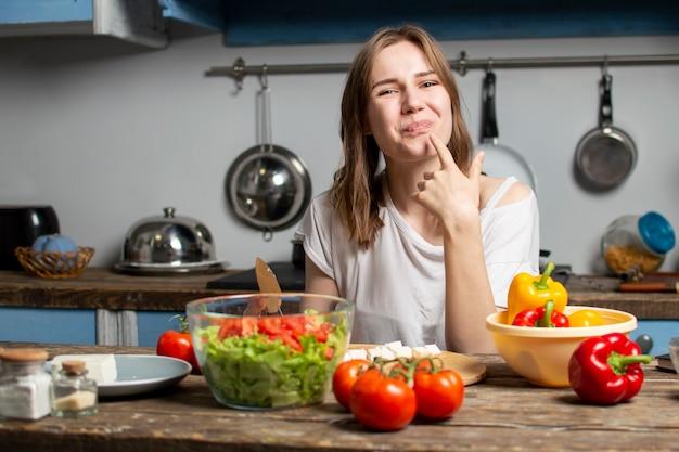 Jovem mulher prepara uma salada vegetariana na cozinha, ela lambe o dedo e gostos, o processo de preparar alimentos saudáveis