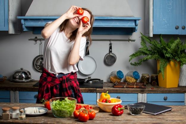 Jovem mulher prepara uma salada vegetariana na cozinha, o processo de preparar alimentos saudáveis
