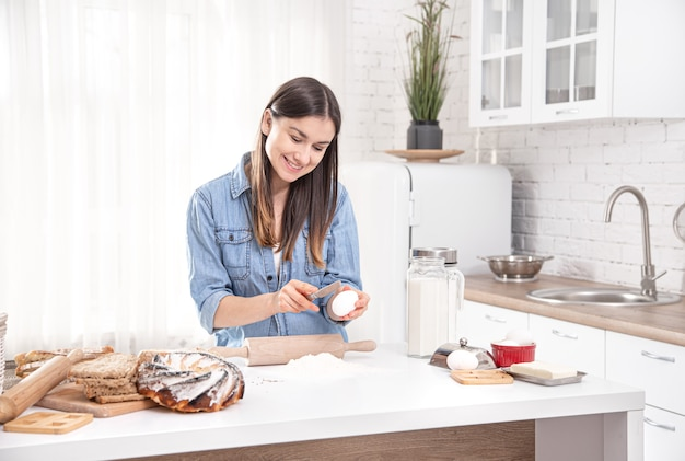 Jovem mulher preparando bolos caseiros na espaçosa cozinha bem iluminada.