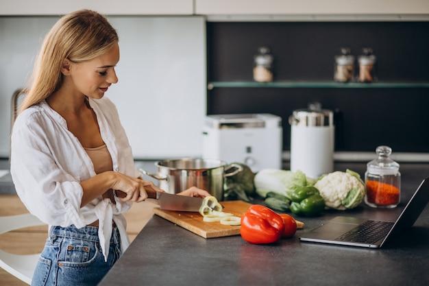 Jovem mulher preparando comida na cozinha